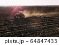 Farm tractor raising dust with harrow plow preparing land for sowing. Agriculture industry, cultivation of land. 64847433