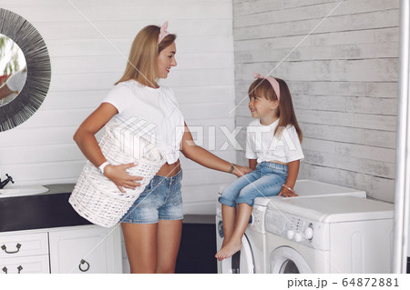 Mother and daughter in a bathroom near wash mashine 64872881