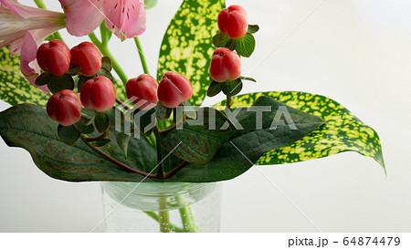 花瓶に挿した小さな春のブーケ:赤いヒペリカム 64874479