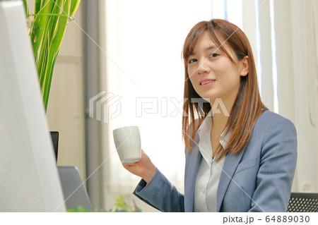 コーヒーカップを持つビジネスウーマン 64889030