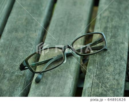 公園のウッドテーブルの上においてあるパソコン用メガネ 64891626