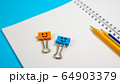Blue and Orange Color Smile Binder Clips with Pencils on Paper Notepad 64903379