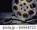 35 mm film reel with dramatic lighting on a dark 64948725
