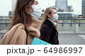 Epidemic control social workers. Two young Caucasian female doctors in face masks walk on city street during quarantine. 64986997