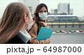 Side view two young Caucasian doctor women wearing face masks, walking on empty city street with clipboards on lockdown. 64987000