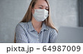 Young Caucasian doctor woman working from home online using laptop, consulting people on quarantine wearing face mask. 64987009