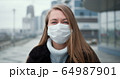 Epidemic quarantine. Portrait of young Caucasian woman wearing mask outdoors, turning head to camera in empty street. 64987901