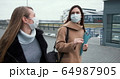 Social activism during coronavirus crisis. Two Caucasian female doctors walk on empty city street in medical face masks. 64987905