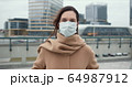 COVID-19 epidemic protection, danger and fear atmosphere. Portrait of beautiful Caucasian woman putting mask on outside. 64987912