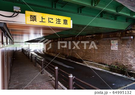 東京都港区新橋・汐留にある線路の「頭上に注意」と書かれた看板のある高架下 64995132