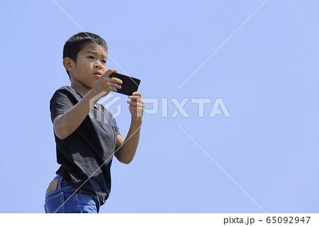 スマホで写真を撮る小学生(5年生)と青空 65092947
