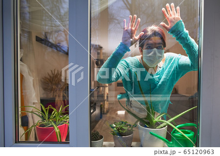 Woman with medical mask on their faces looking through window, selfisolation to prevent spread infection. 65120963
