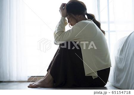床に座って落ち込む女性 65154718