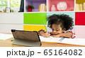 Young African American kid girl studying using digital tablet, preschool child homeschooling concept 65164082