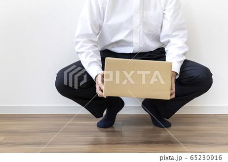 ダンボールと床に座っているワイシャツを着た男性 65230916