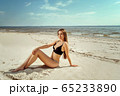 Young and sensual woman enjoying sunny day on tropical beach 65233890