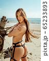Sexy girl on the beach in bikini 65233893