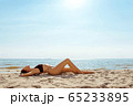 Young and sensual woman enjoying sunny day on tropical beach 65233895