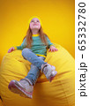 Stylish little girl resting on bean bag 65332780