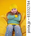 Stylish little girl resting on bean bag 65332784