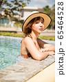 プールサイドでリラックスをする水着姿の女性 65464528
