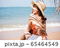 浜辺に座る水着姿の女性 65464549