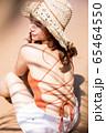 浜辺に座る水着姿の女性 65464550