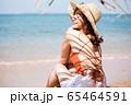 浜辺に座る水着姿の女性 65464591