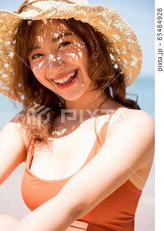 浜辺に座る水着姿の女性 65464926