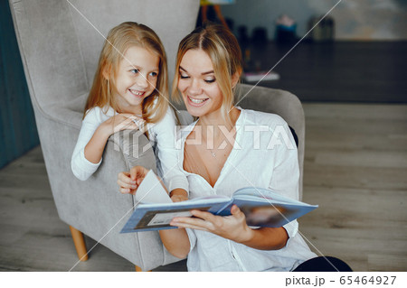 Mother reading a book with daughter 65464927