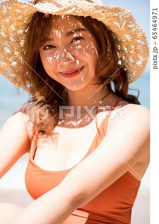 浜辺に座る水着姿の女性 65464971