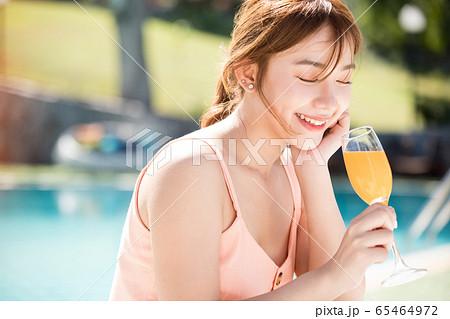 リゾート旅行を楽しむプールサイドの若い女性 65464972