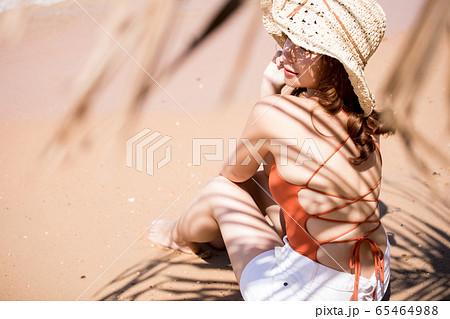 浜辺に座る水着姿の女性 65464988