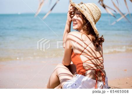 浜辺に座る水着姿の女性 65465008