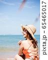 浜辺に座る水着姿の女性 65465017