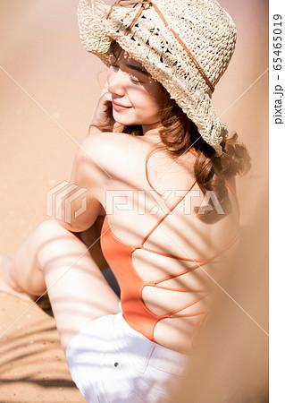 浜辺に座る水着姿の女性 65465019