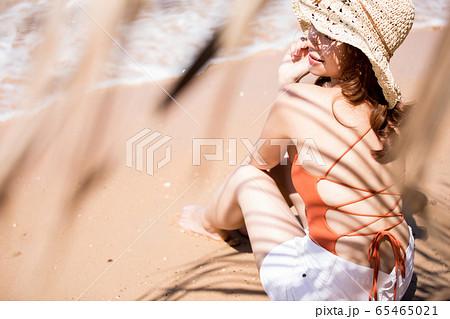 浜辺に座る水着姿の女性 65465021