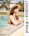 プールサイドでリラックスをする水着姿の女性 65465057