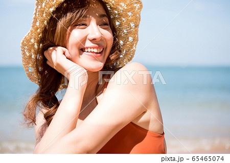 浜辺に座る水着姿の女性 65465074