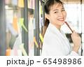 若い きれい 女性 会社員 笑顔 付箋 窓 貼る メモ ペン 人物 素材 65498986