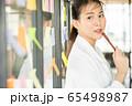 若い きれい 女性 会社員 笑顔 付箋 窓 貼る メモ ペン 人物 素材 65498987