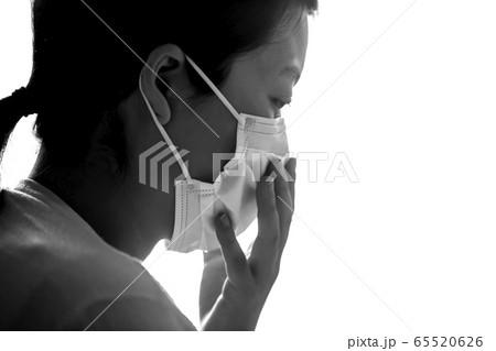 白いマスクをした女性の横顔の白黒のアップとコピースペース 65520626