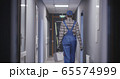 Janitor cleaning a corridor 65574999