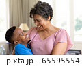 Senior mixed race woman and her grandson enjoying their time at home 65595554