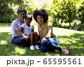 Multi-generation mixed race family enjoying their time at a garden 65595561