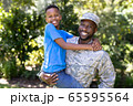 African American man wearing a military uniform holding his son 65595564