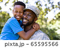 African American man wearing a military uniform holding his son 65595566