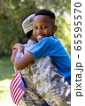 African American man wearing a military uniform holding his son 65595570