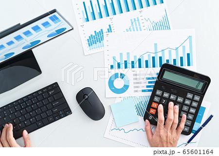 電卓を使う男性の手の俯瞰。金融と会計のイメージ。デスクトップパソコンのモニターやレポートに多数のグラ 65601164