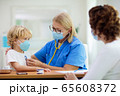 Doctor examining sick child in face mask 65608372